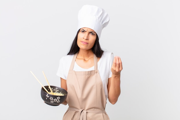 Pretty hispanic chef woman making capice or money gesture, telling you to pay and holding a noodle bowl