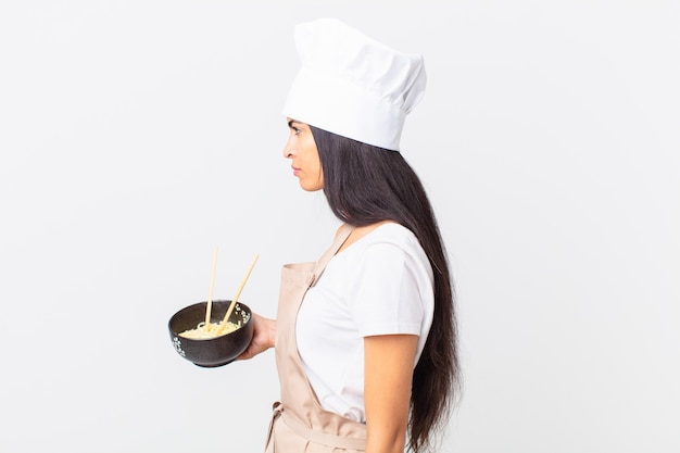 Pretty hispanic chef woman on profile view thinking, imagining or daydreaming and holding a noodle bowl