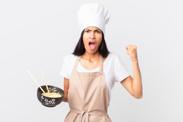 Pretty hispanic chef woman shouting aggressively with an angry expression and holding a noodle bowl