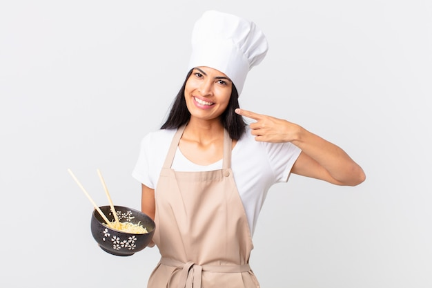 Pretty hispanic chef woman smiling confidently pointing to own broad smile and holding a noodle bowl