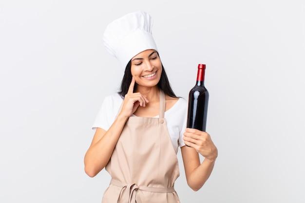 Довольно латиноамериканская женщина-повар счастливо улыбается и мечтает или сомневается и держит бутылку вина