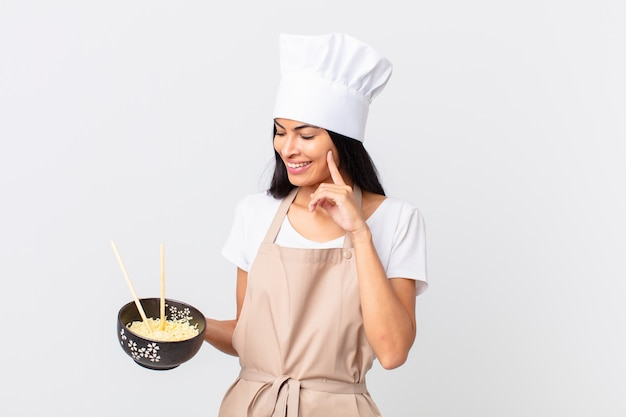 Pretty hispanic chef woman smiling happily and daydreaming or doubting and holding a noodle bowl