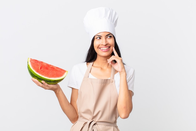Pretty hispanic chef woman smiling happily and daydreaming or doubting and holding a watermelon