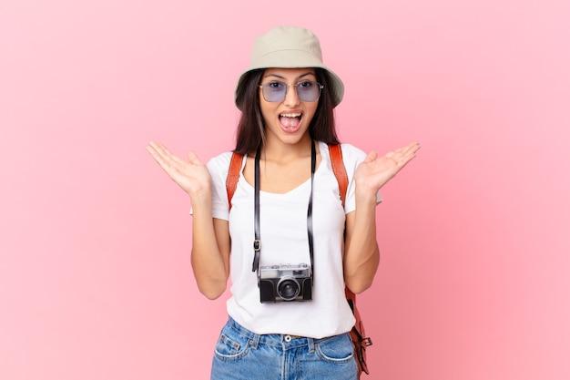 写真カメラと帽子で信じられない何かに幸せと驚きを感じているかなりヒスパニック系の観光客