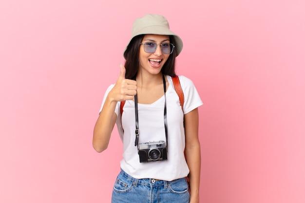 Симпатичная латиноамериканская туристка гордится собой, позитивно улыбается, показывает палец вверх с фотоаппаратом и в шляпе