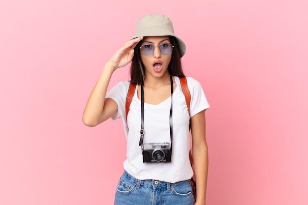 写真カメラと帽子で幸せ、驚き、驚きに見えるかなりヒスパニック系の観光客