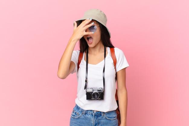 ショックを受けたり、怖がったり、恐怖を感じたり、写真カメラと帽子で顔を手で覆っているかなりヒスパニック系の観光客