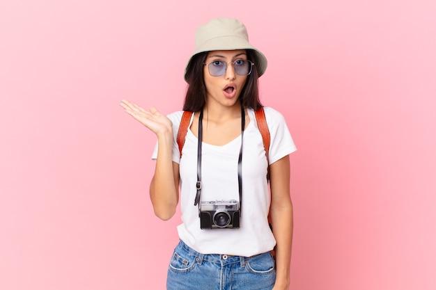 写真カメラと帽子でオブジェクトを持って顎を落とし、驚いてショックを受けたように見えるかなりヒスパニック系の観光客