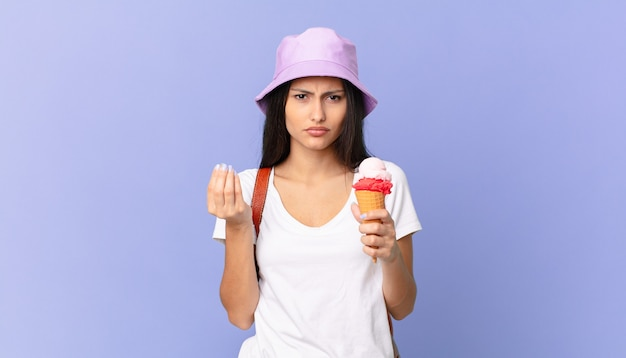 Pretty hispanic tourist making capice or money gesture, telling you to pay and holding an ice cream