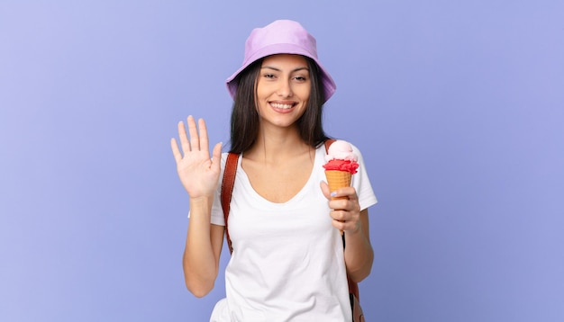 Pretty hispanic tourist smiling happily, waving hand, welcoming and greeting you and holding an ice cream