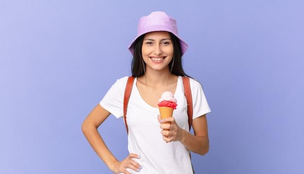 かなりヒスパニック系の観光客が腰に手を当てて幸せそうに笑って自信を持ってアイスクリームを持っています