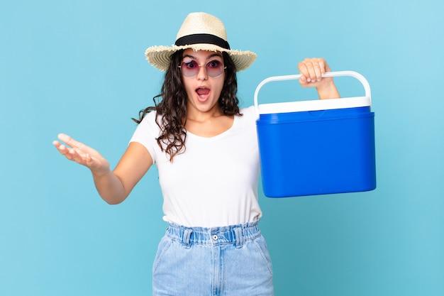 꽤 히스패닉계 여성이 휴대용 냉장고를 들고 있는 믿을 수 없는 놀라움에 놀라고, 충격을 받았으며, 놀랐습니다.