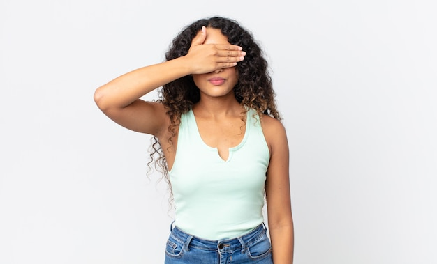 片手で目を覆っているかなりヒスパニック系の女性が怖い、不安を感じている、不思議に思っている、または盲目的に驚きを待っている