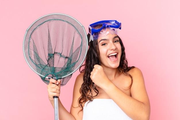 Довольно латиноамериканская женщина чувствует себя счастливой и сталкивается с проблемой или празднует в очках и рыболовной сети