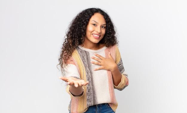 かなりヒスパニック系の女性が幸せで恋をしていて、片方の手が心臓の横に、もう片方の手が前に伸びて笑っています