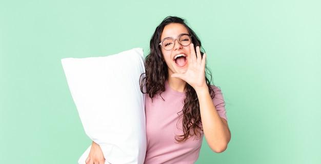 Симпатичная латиноамериканка чувствует себя счастливой, громко кричит, прижав руки ко рту и одетая в пижаму с подушкой