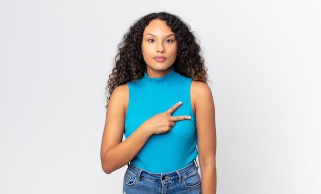 幸せ、前向き、成功を感じているかなりヒスパニック系の女性、胸の上に手でv字型を作り、勝利または平和を示しています