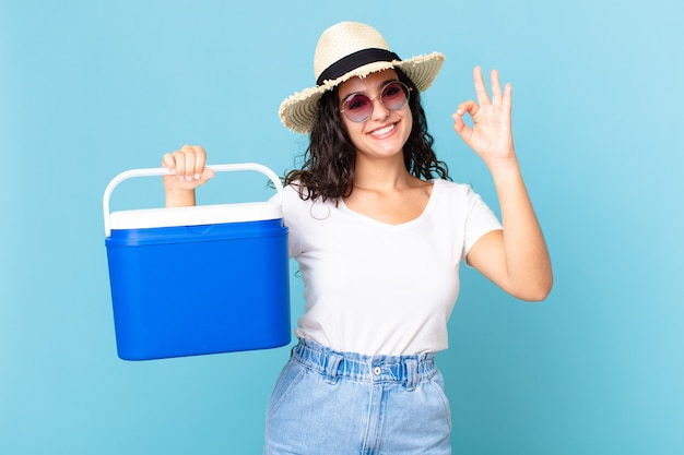 꽤 히스패닉계 여성이 행복감을 느끼고 휴대용 냉장고를 들고 괜찮은 제스처로 승인을 보여줍니다