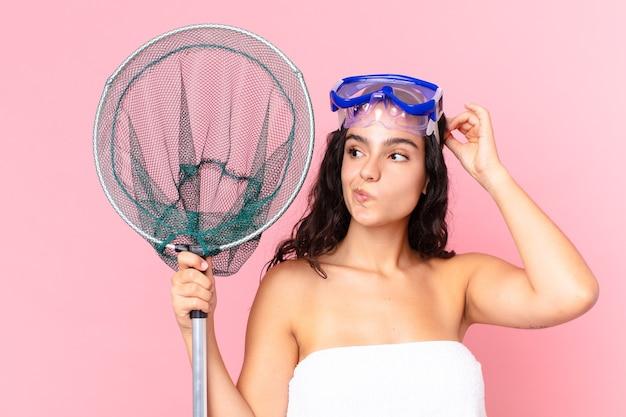 Довольно латиноамериканская женщина чувствует себя озадаченной и сбитой с толку, почесывая голову в очках и рыболовной сети