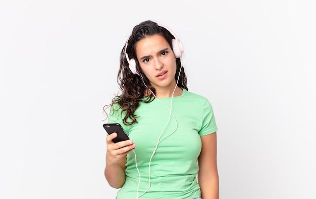 ヘッドフォンとスマートフォンに戸惑い、混乱しているかなりヒスパニック系の女性