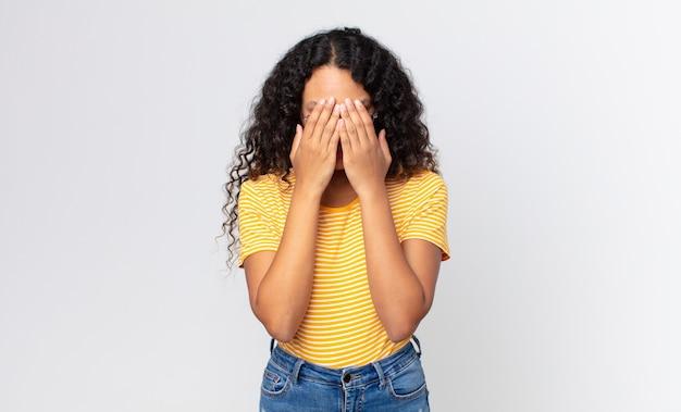 예쁜 히스패닉계 여성은 슬프고, 좌절하고, 긴장하고, 우울하고, 두 손으로 얼굴을 가리고, 울고 있다