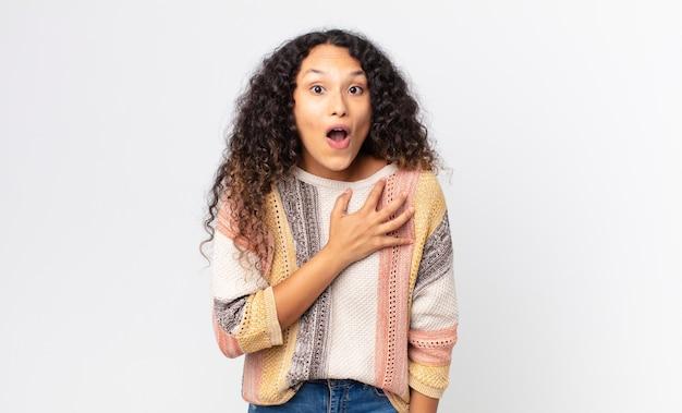 かなりヒスパニック系の女性は、ショックを受けて驚き、笑顔で、心に手を取り合って、一人になって幸せであるか、感謝の気持ちを示しています