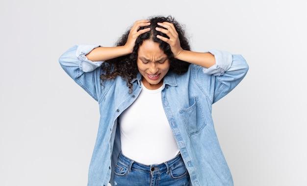 かなりヒスパニック系の女性は、ストレスや欲求不満を感じ、手を頭に上げ、疲れ、不幸、片頭痛を感じています