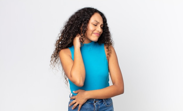 Симпатичная латиноамериканка чувствует стресс, разочарование и усталость, трет болезненную шею, с встревоженным и встревоженным взглядом