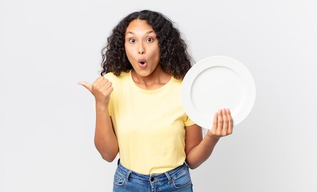 空のきれいな皿を持っているかなりヒスパニック系の女性