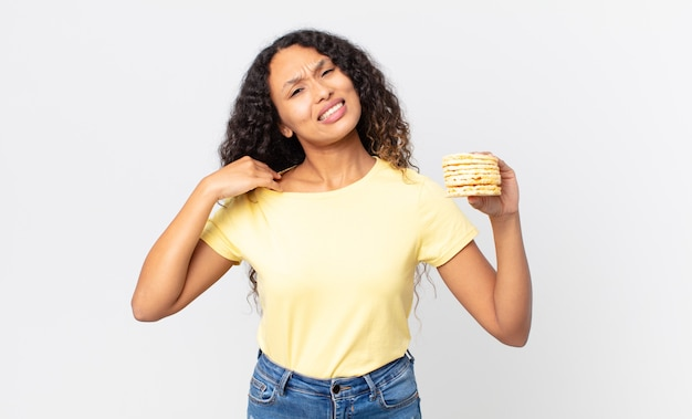 Pretty hispanic woman holding a rice diet cakes