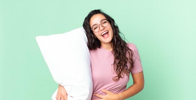 Симпатичная латиноамериканка громко смеется над веселой шуткой и носит пижаму с подушкой