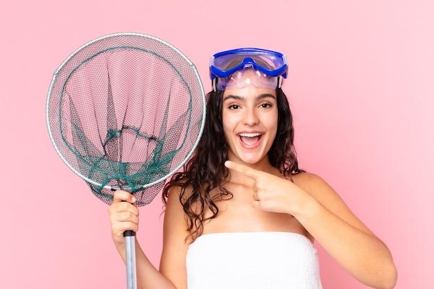Симпатичная латиноамериканская женщина выглядит взволнованной и удивленной, указывая в сторону с очками и рыболовной сетью