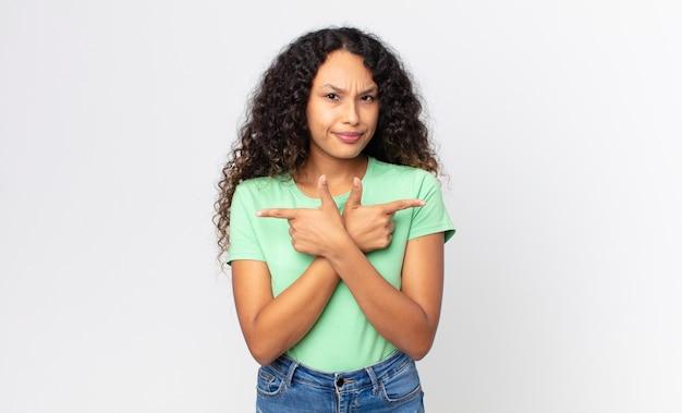 Симпатичная латиноамериканская женщина выглядит озадаченной и сбитой с толку, неуверенной в себе и с сомнениями указывает в противоположные стороны