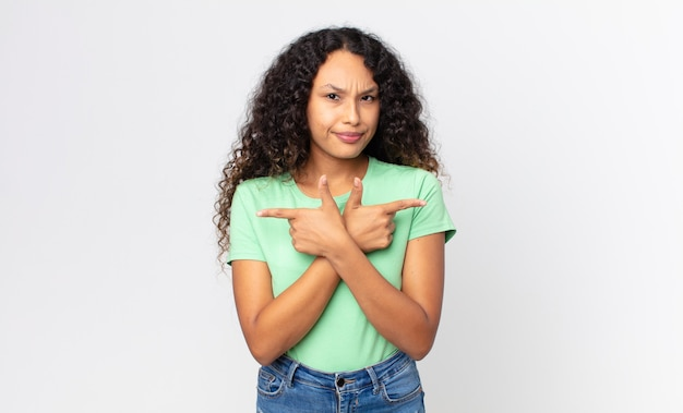 Pretty hispanic woman looking puzzled and confused, insecure and pointing in opposite directions with doubts