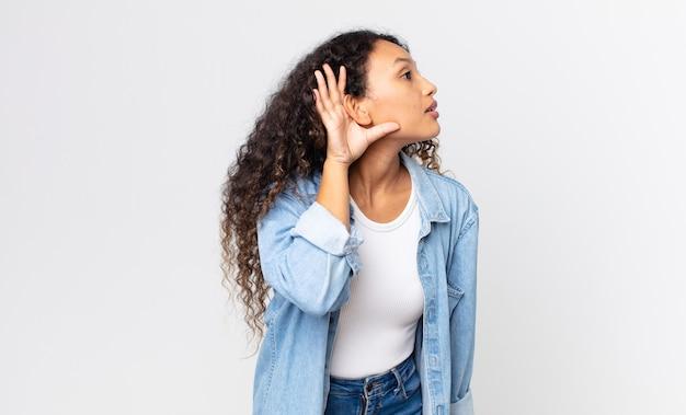 Довольно латиноамериканская женщина выглядит серьезной и любопытной, слушает, пытается услышать секретный разговор или сплетню, подслушивает
