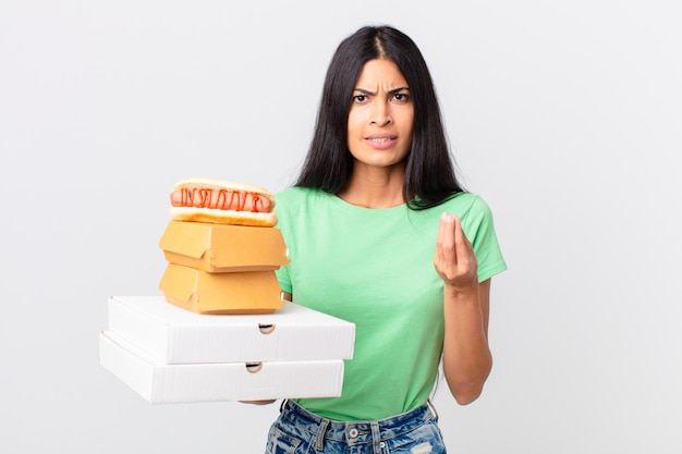 Довольно латиноамериканская женщина делает капризный или денежный жест, говорит вам заплатить и держит коробки быстрого питания на вынос