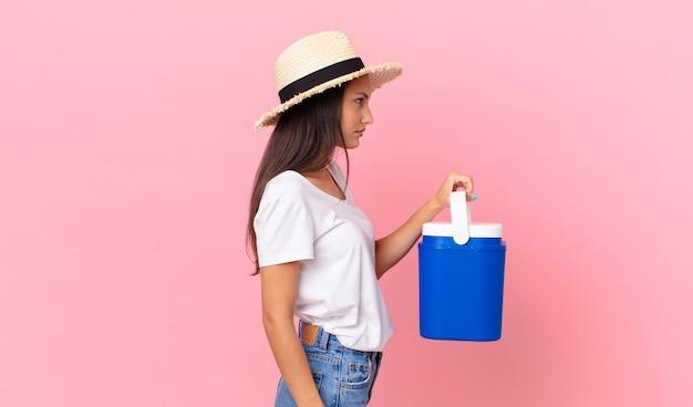 프로필 보기에 예쁜 히스패닉 여성, 생각, 상상 또는 공상을 하고 휴대용 냉장고를 들고