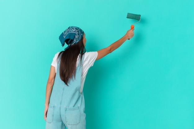 Pretty hispanic woman painting a wall