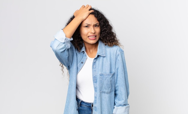 Pretty hispanic woman raising palm to forehead thinking oops, after making a stupid mistake or remembering, feeling dumb