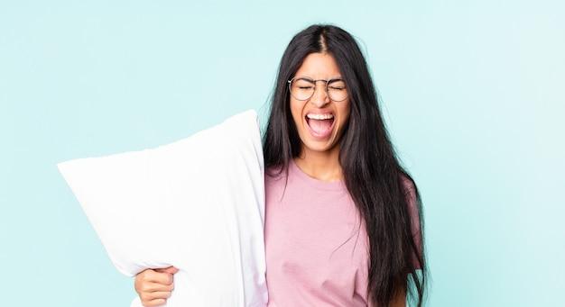 Довольно латиноамериканская женщина агрессивно кричит, выглядит очень сердитой и носит пижаму с подушкой