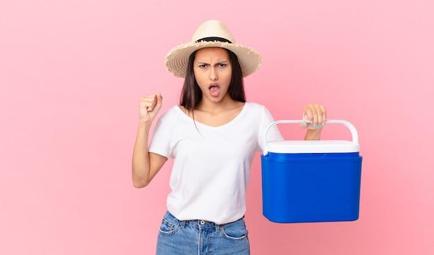 화난 표정으로 공격적으로 소리를 지르고 휴대용 냉장고를 들고 있는 예쁜 히스패닉 여성