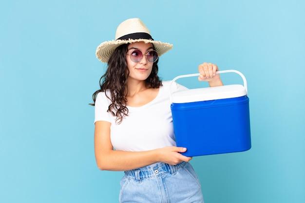 かなりヒスパニック系の女性が肩をすくめ、混乱し、携帯用冷蔵庫を持っていると不安を感じる