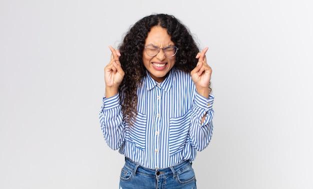 예쁜 히스패닉계 여성이 웃고 걱정스럽게 두 손가락을 교차하며 걱정하고 행운을 빌거나 바라고 있습니다.