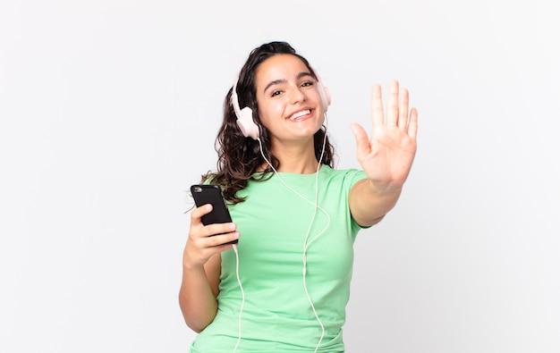 Довольно латиноамериканская женщина улыбается и выглядит дружелюбно, показывая номер пять в наушниках и смартфоне