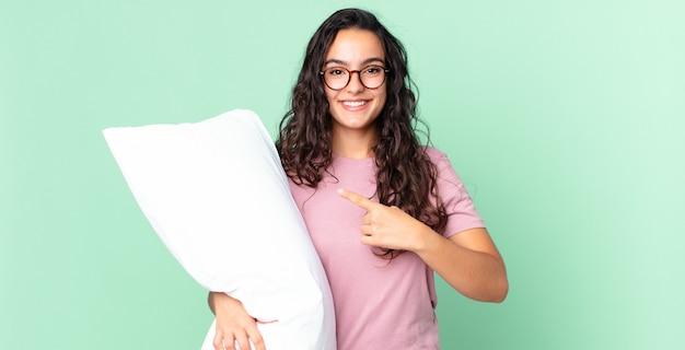 Довольно латиноамериканская женщина весело улыбается, чувствует себя счастливой и указывает в сторону и носит пижаму с подушкой
