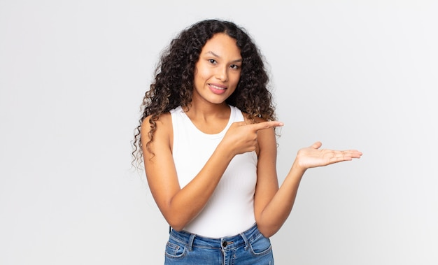 Pretty hispanic woman smiling, feeling happy, carefree and satisfied, pointing to concept or idea on copy space on the side