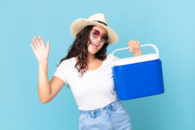 예쁜 히스패닉계 여성이 행복하게 웃고, 손을 흔들며, 휴대용 냉장고를 들고 당신을 환영하고 인사합니다.