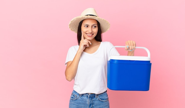 턱에 손을 대고 휴대용 냉장고를 들고 행복하고 자신감 있는 표정으로 웃고 있는 예쁜 히스패닉 여성