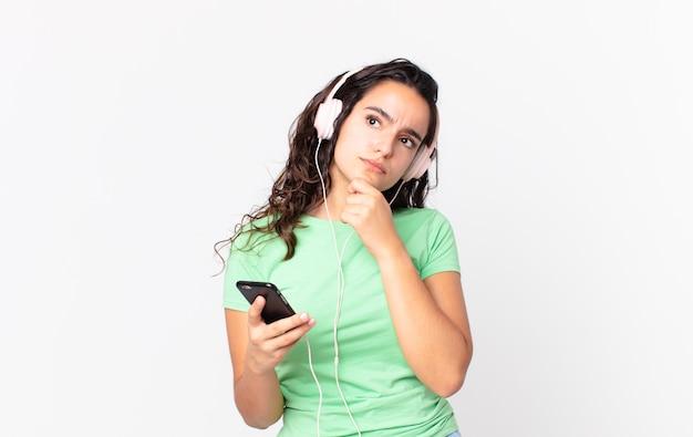 Довольно латиноамериканская женщина думает, сомневается и смущается с наушниками и смартфоном
