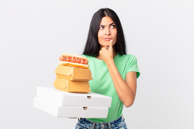 Pretty hispanic woman thinking, feeling doubtful and confused and holding take away fast food boxes